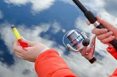 Manos femeninas que llevan a cabo una caña de pescar y un señuelo Imagen de archivo