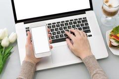 Manos femeninas que mecanografían el teclado del ordenador portátil y que sostienen el teléfono con isola Imagenes de archivo