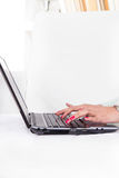 Manos femeninas que mecanografían en el teclado del ordenador portátil con la manicura roja Fotos de archivo libres de regalías