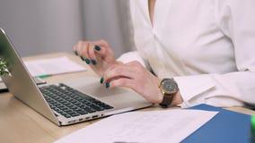 Manos femeninas que mecanografían en el teclado del ordenador portátil en oficina