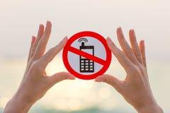 Manos femeninas que no llevan a cabo ningún indicativo de teléfono en la playa Foto de archivo libre de regalías