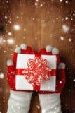 Manos femeninas que ofrecen el regalo de la Navidad Fotografía de archivo libre de regalías