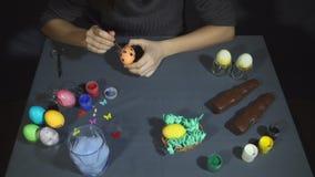 Manos femeninas que pintan la decoración del huevo para pascua sobre un fondo gris almacen de video