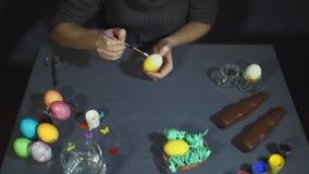 Manos femeninas que pintan la decoración del huevo para pascua sobre un fondo gris almacen de metraje de vídeo