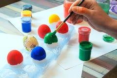 Manos femeninas que pintan los huevos de Pascua Fotos de archivo libres de regalías