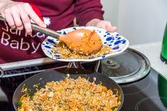Manos femeninas que ponen porciones cocinadas del buckweat a las placas coloridas sobre la cocina eléctrica moderna en cocina Foto de archivo libre de regalías