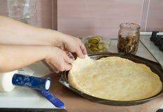 Manos femeninas que preparan la pasta para la pizza, cocina casera Imagen de archivo libre de regalías