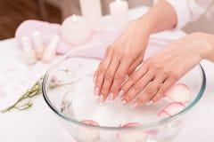 Manos femeninas que reciben el tratamiento del balneario en bol de vidrio con los pétalos color de rosa Fotografía de archivo libre de regalías