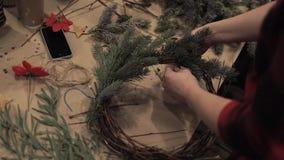 Manos femeninas que refuerzan ramas del pino en la guirnalda de la Navidad