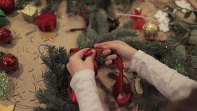 Manos femeninas que refuerzan una cinta roja en una guirnalda de la Navidad