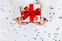 Manos femeninas que se sostienen presentes con el arco rojo Foto de archivo libre de regalías