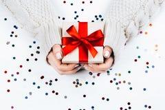 Manos femeninas que se sostienen presentes con el arco rojo Fotos de archivo libres de regalías