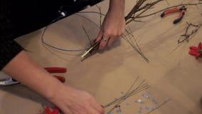 Manos femeninas que se unen a las barras de madera con un alambre azul que hace la guirnalda