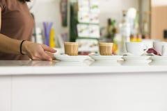 Manos femeninas que sirven los cafés en una cafetería foto de archivo