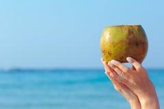 Manos femeninas que sostienen el coco en fondo del mar Foto de archivo libre de regalías