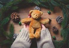 Manos femeninas que sostienen el juguete teddybear de la Navidad Imagen de archivo