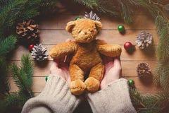 Manos femeninas que sostienen el juguete teddybear de la Navidad Imagenes de archivo