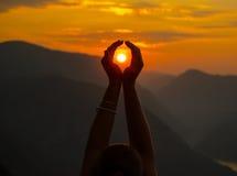 Manos femeninas que sostienen el sol Foto de archivo libre de regalías