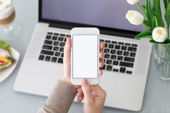 Manos femeninas que sostienen el teléfono con la pantalla aislada cerca del ordenador portátil Fotografía de archivo