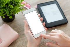Manos femeninas que sostienen el teléfono con la pantalla en la tabla de las mujeres Imagen de archivo libre de regalías