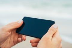 Manos femeninas que sostienen el teléfono con la pantalla táctil en el fondo Imagen de archivo libre de regalías