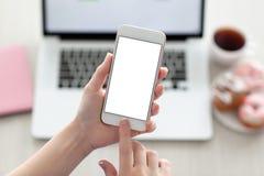 Manos femeninas que sostienen el teléfono con la pantalla y el ordenador portátil Fotografía de archivo libre de regalías