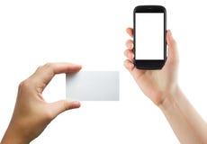 Manos femeninas que sostienen el teléfono móvil con la pantalla aislada y la tarjeta de crédito en blanco del negocio aisladas en Foto de archivo