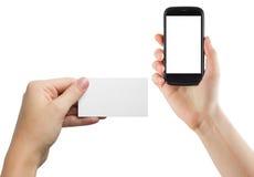Manos femeninas que sostienen el teléfono móvil con la pantalla aislada y la tarjeta de crédito en blanco del negocio aisladas en Imagenes de archivo
