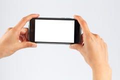 Manos femeninas que sostienen el teléfono móvil horizontalmente Imágenes de archivo libres de regalías