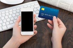 Manos femeninas que sostienen el teléfono y la tarjeta de crédito sobre la tabla adentro apagado Foto de archivo
