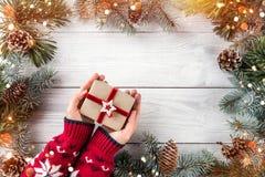 Manos femeninas que sostienen la caja de regalo de la Navidad en el fondo de madera blanco con las ramas del abeto, conos del pin imagen de archivo