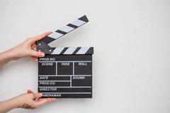 Manos femeninas que sostienen la chapaleta de la película en blanco Imágenes de archivo libres de regalías