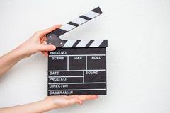 Manos femeninas que sostienen la chapaleta de la película en blanco Imagen de archivo