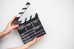 Manos femeninas que sostienen la chapaleta de la película en blanco Foto de archivo