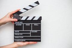 Manos femeninas que sostienen la chapaleta de la película en blanco Imagen de archivo libre de regalías