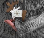 Manos femeninas que sostienen la decoración de la Navidad del reno Fotos de archivo libres de regalías