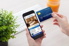 Manos femeninas que sostienen la reservación de hotel del app del teléfono y la tarjeta de crédito imagen de archivo