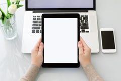 Manos femeninas que sostienen la tableta del ordenador con la pantalla aislada cerca de l Foto de archivo libre de regalías