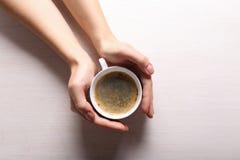 Manos femeninas que sostienen la taza de café Imagen de archivo libre de regalías