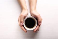 Manos femeninas que sostienen la taza de café en fondo de madera Imagen de archivo libre de regalías