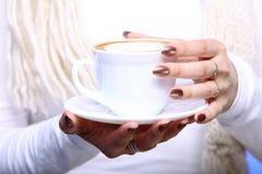 Manos femeninas que sostienen la taza de capuchino caliente del café del latte Imagenes de archivo