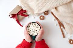 Manos femeninas que sostienen la taza de chocolate caliente con la melcocha Bebida de la Navidad, galletas sabrosas, caja de rega imágenes de archivo libres de regalías