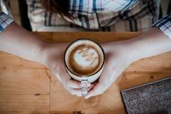 Manos femeninas que sostienen las tazas de café fotografía de archivo