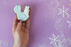 Manos femeninas que sostienen poco pan de jengibre del gallo de la Navidad Imagen de archivo libre de regalías