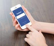 Manos femeninas que sostienen un iPhone blanco con Facebook en la pantalla imagen de archivo