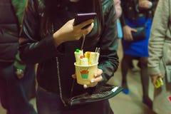 Manos femeninas que sostienen un smartphone y que hacen una foto de d cocinada Fotografía de archivo libre de regalías