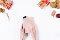 Manos femeninas que sostienen una bolsa de papel con un regalo del ` s del Año Nuevo Fotografía de archivo libre de regalías