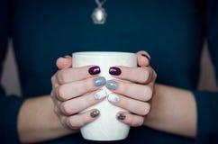 Manos femeninas que sostienen una taza blanca Fotos de archivo libres de regalías