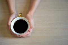 Manos femeninas que sostienen una taza de café con café del café express en la tabla de madera Fotos de archivo