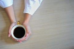 Manos femeninas que sostienen una taza de café con café del café express en la tabla de madera Fotografía de archivo libre de regalías